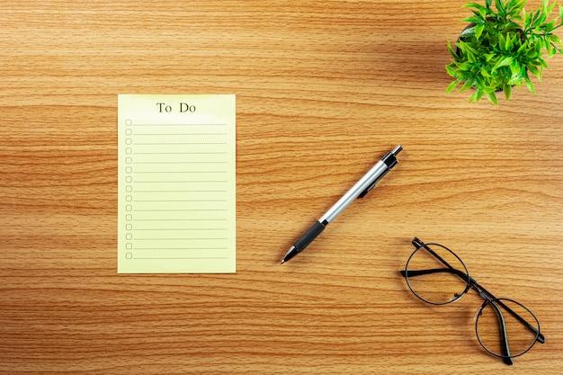 Vaciar para hacer la lista y una pluma en el escritorio de madera.