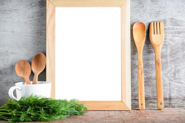 Vacie los accesorios aislados blancos de madera del marco y de la cocina en una tabla de madera.