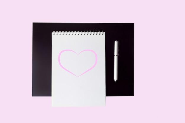 Vacie el blanco abierto con el cuaderno rosado del corazón con la pluma en la opinión superior del fondo rosado.