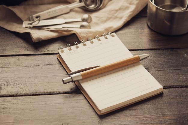 Vacie el cuaderno del espacio blanco con las herramientas de la panadería de la pluma y de los pasteles en fondo de madera.