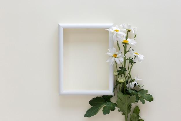 Vacie el marco blanco con las flores encima aisladas en el fondo blanco