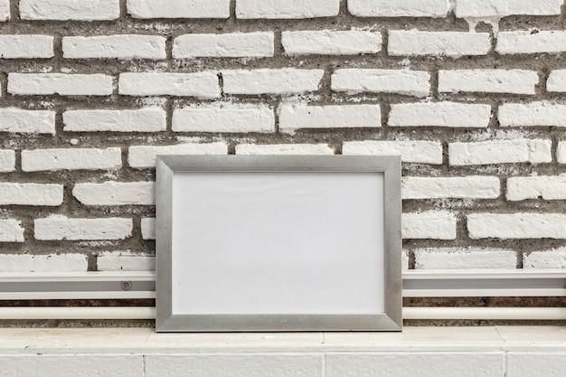 Vacíe el marco blanco en la pared de ladrillos grunge, simúlpelo para mostrar o el montaje de su contenido.