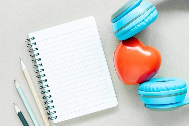 Vacíe la página abierta del cuaderno del libro blanco con los lápices y el corazón rojo con el auricular en la tabla blanca.