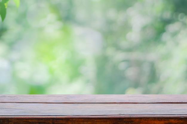 Vacie la sobremesa de madera de la cubierta en fondo abstracto borroso verde del fondo del follaje.