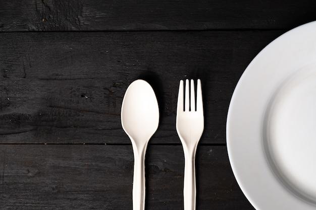 Vacie el tazón de fuente, la bifurcación y la cuchara blancos en la tabla de madera negra, opinión del primer. concepto de dieta: plano de platos de cocina limpios sobre una superficie rústica oscura