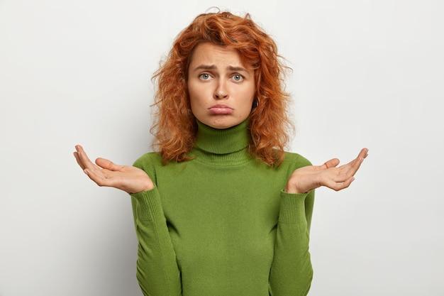 Vacilación y confusión. triste mujer pelirroja disgustada se encoge de hombros, no puede tomar una decisión