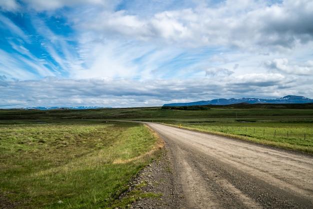 Vacío camino de tierra a través del paisaje rural.