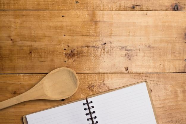 Vacío libro blanco de libro y cuchara en madera en blanco