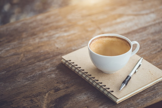Vacío de taza de café de cerámica blanca en mesa de madera