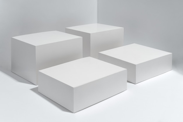 Vacíos cuatro cubos de plataforma blanca sobre fondo blanco.