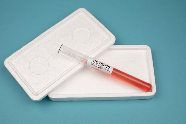 La vacuna contra el caronavirus covid-19 se encuentra en una caja fuerte sobre una mesa azul. concepto médico y sanitario.