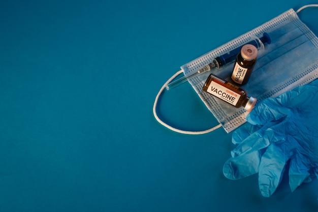 Vacuna contra el coronavirus en botellas sobre fondo azul con espacio de copia. viales para covid19