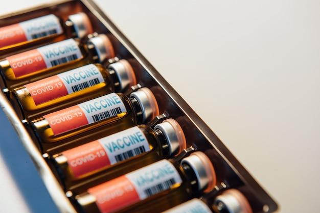 Vacuna contra el coronavirus en el paquete, primer plano. frascos de medicina covid19 se encuentran en fila, fondo blanco.