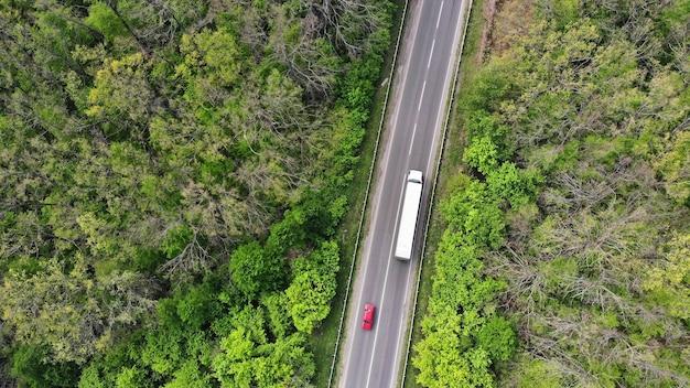 Vagón y coche rojo conduciendo por la carretera.