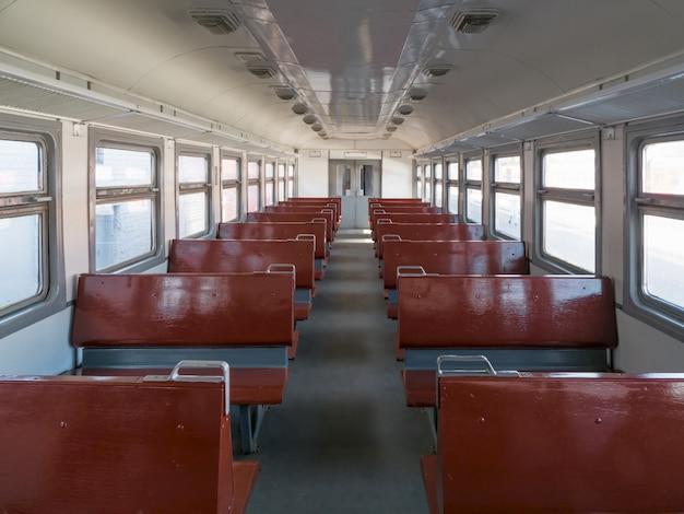 Vagón de tren vacío con perspectiva de asientos
