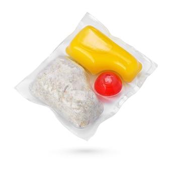 Vaina de detergente para ropa de color amarillo y rojo aislado sobre fondo blanco.