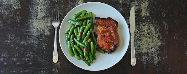 Vainas de guisante verde y filete del cerdo en una placa. dieta ceto.