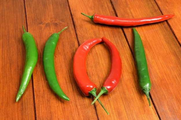Vainas rojas y verdes de chiles frescos presentaron la palabra caliente en una mesa de madera marrón
