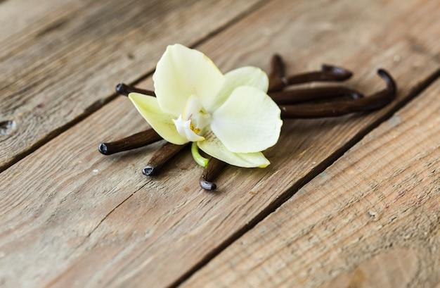 Vainas de vainilla secas y orquídea de vainilla en mesa de madera