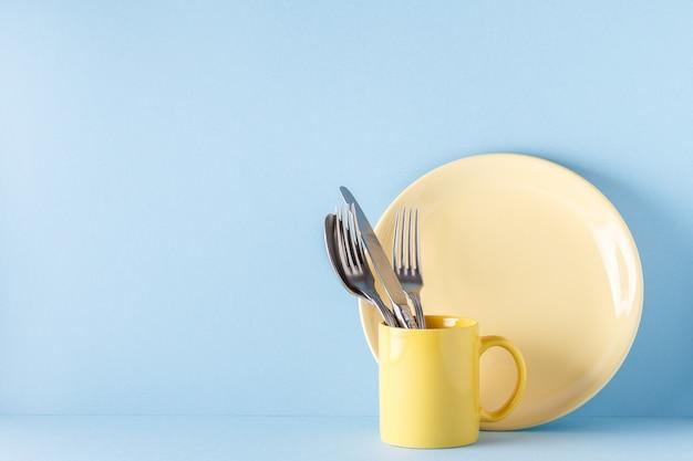 Vajilla y cubertería sobre un fondo azul pastel