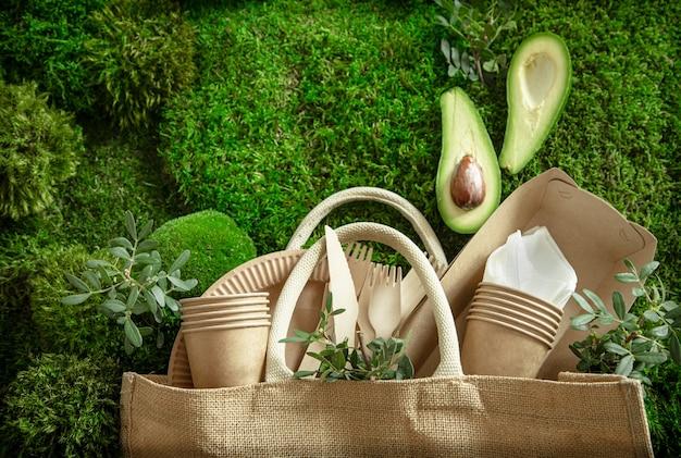 Vajilla ecológica, desechable y reciclable. cajas de comida de papel, platos y cubiertos de maicena sobre un fondo de hierba verde.