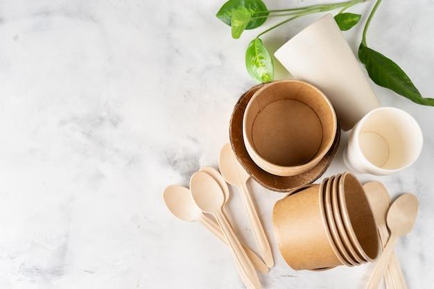 Vajilla ecológica en verde claro. vasos de papel y bambú, bolsa y cubiertos de madera.