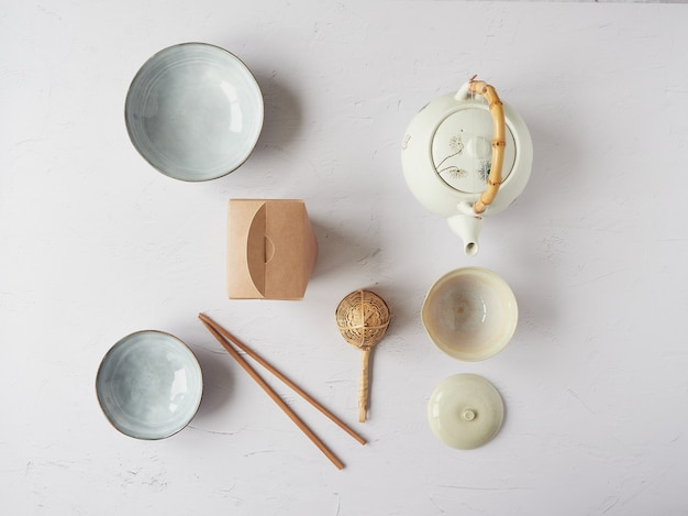 Vajilla oriental. tetera japonesa y china, cuencos, palillos, colador de bambú y recipiente de cartón. vista superior