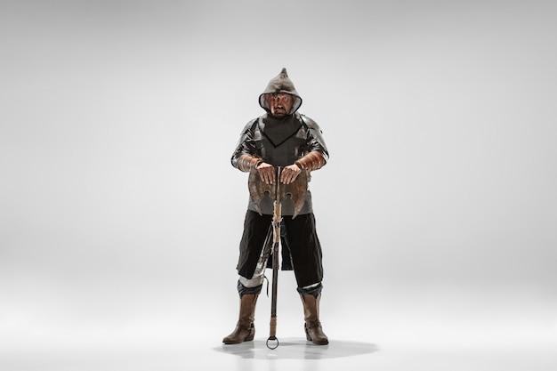 Valiente caballero acorazado con lucha con armas profesionales aislado sobre fondo blanco de estudio.