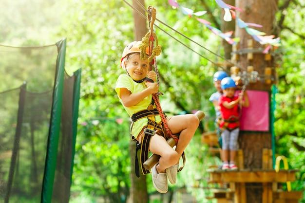 Valiente jovencita en casco se sube a las copas de los árboles en el parque de atracciones de cuerda en las vacaciones de verano, campamento infantil