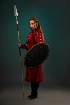 Valiente mujer guerrera con arma posando en el estudio.
