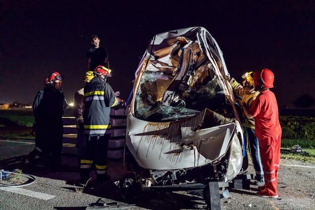Valientes bomberos intentando liberar al hombre del coche accidentado.