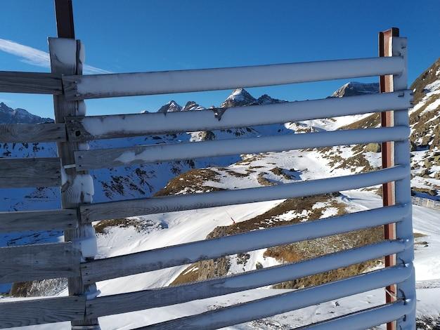 Valla de madera cubierta de nieve detrás de las montañas