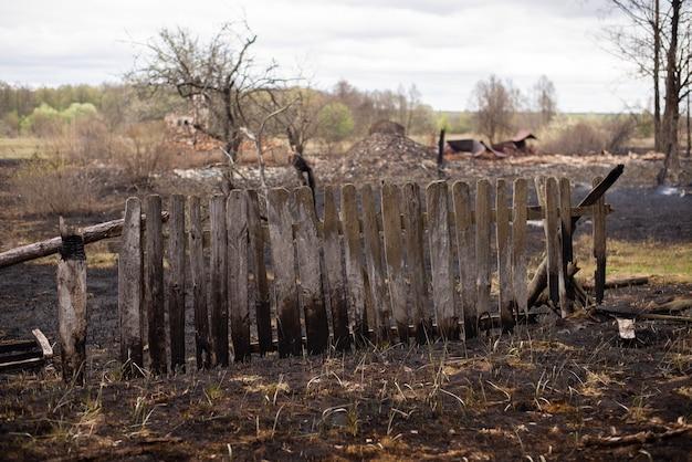 Valla de madera quemada negra, mucha basura dañada
