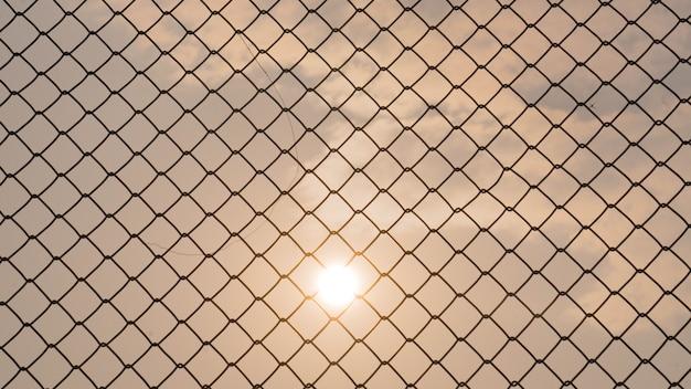 Valla de malla con puesta de sol.