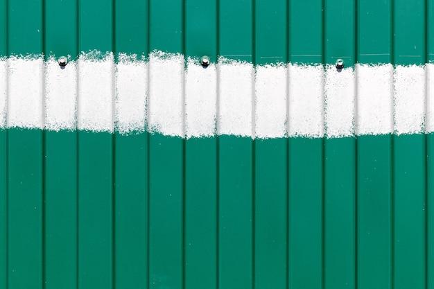 Valla de metal verde con rayas verticales onduladas