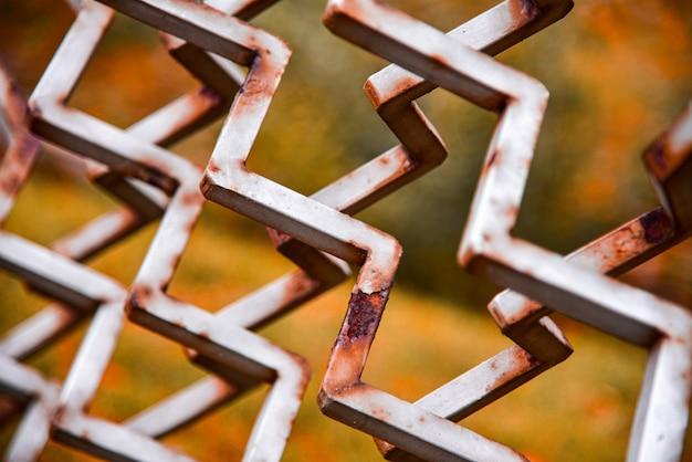 Valla metálica oxidada hecha de varillas de hierro, primer plano