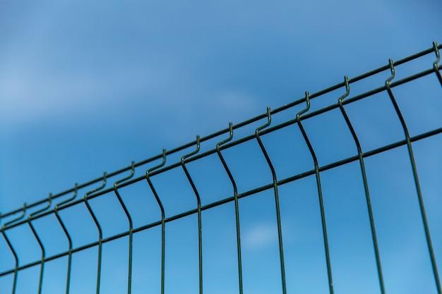 Valla de rejilla de acero con alambre contra el cielo azul.
