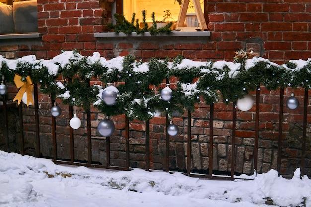 Vallado de ventanas en un edificio vintage decorado con adornos navideños cubiertos de nieve