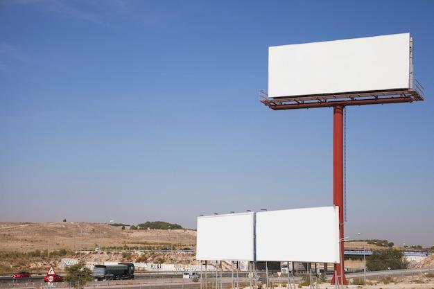 Vallas publicitarias blancas en blanco cerca de la autopista.