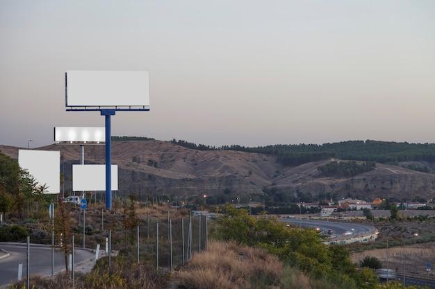 Vallas publicitarias blancas en carretera con montañas al fondo.