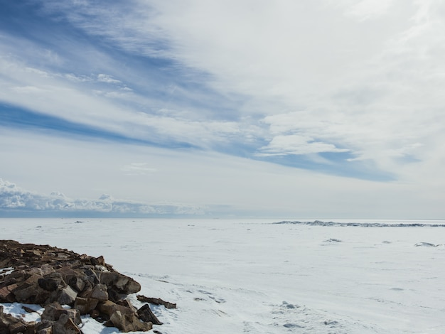 Valle cubierto de nieve en un frío día de invierno bajo el brillante cielo nublado