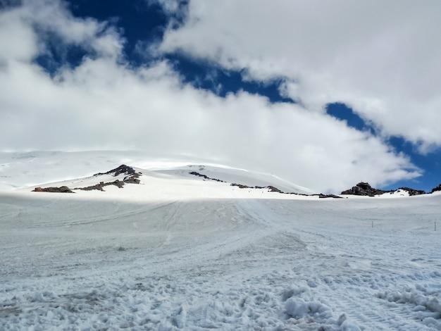 Valle de montaña cubierto de nieve, cubierto de nubes grises. siluetas apenas perceptibles de personas caminando por el valle.