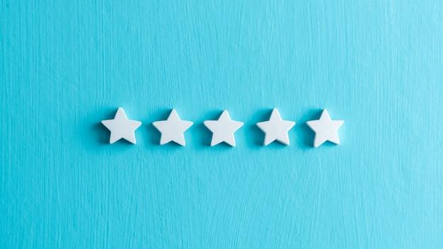 Valoración de la satisfacción del cliente, estrellas blancas sobre fondo azul claro.