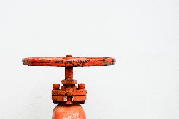 Válvula de agua naranja frente a la pared blanca.