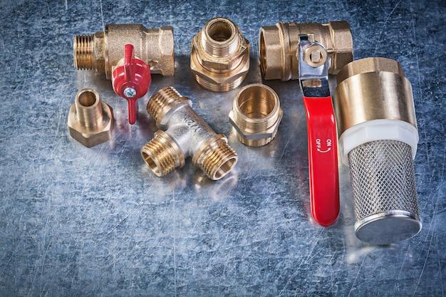 Válvula de bola de palanca de latón, conectores de tubo, filtro colador sobre fondo metálico concepto de fontanería
