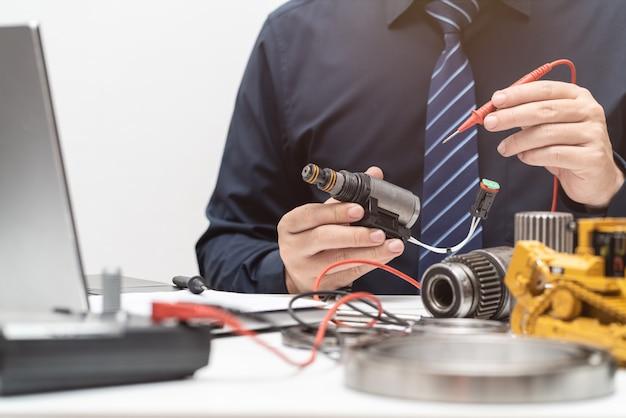 Válvula solenoide de inspección de ingeniero profesional para durante el día de trabajo en la oficina, concepto de reparación de maquinaria pesada de mantenimiento