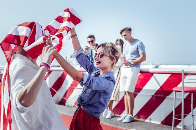 Vamos a bailar. encantadora mujer de pie en posición semi mientras sostiene la bandera americana
