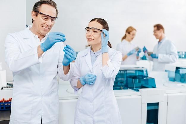 Vamos a demostrarlo. científico masculino encantado positivo manteniendo la sonrisa en su rostro inclinando la cabeza mientras sostiene el tubo de ensayo con ambas manos