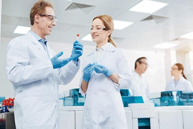 Vamos a probarlo. científico responsable sosteniendo el tubo de ensayo en la mano mientras se lo demuestra a su colega y va a hacer un experimento.