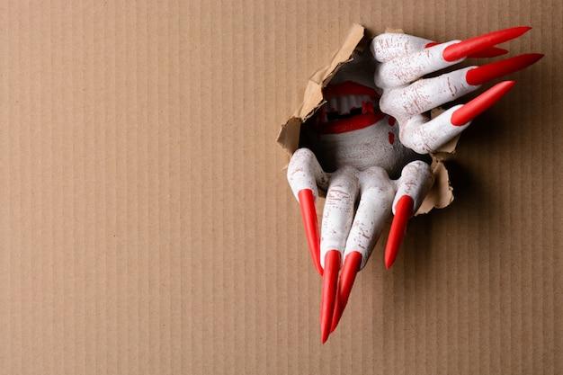Vampiro rasgando cartón con garras afiladas
